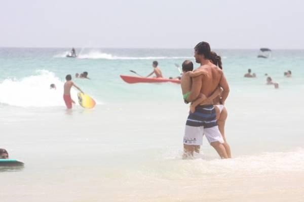 De barrigão, Juliana Paes aproveita praia com o filho e o marido