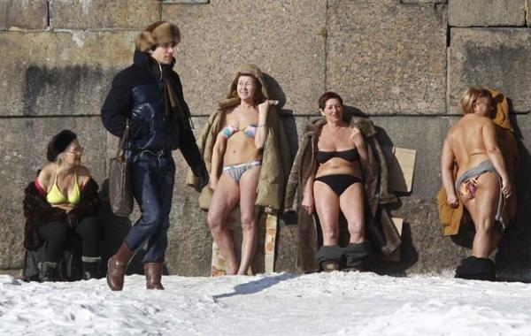 De biquíni e casaco de pele, russas tomam banho de sol na neve