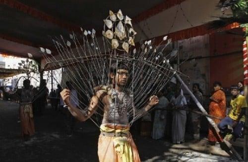 Homens hindus têm o corpo espetado por dezenas de varetas de metal