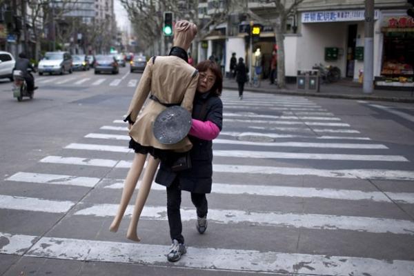 Mulher é flagrada carregando manequim vestido em rua na China
