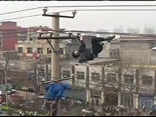 Bêbado se arrisca ao escalar poste com fios de alta tensão na China
