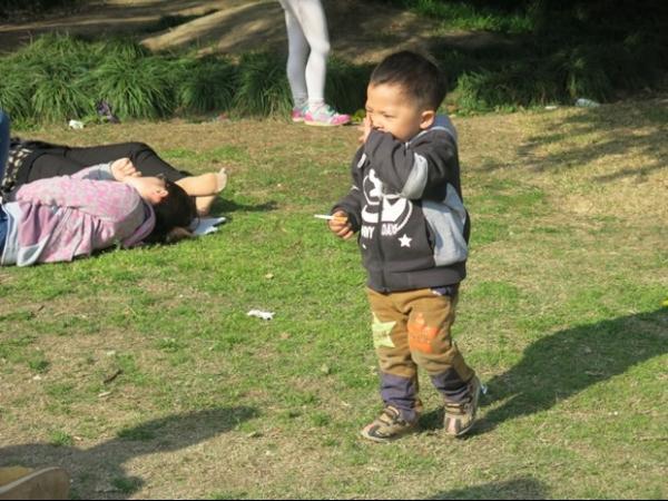Mãe é vista acendendo cigarro para bebê em parque