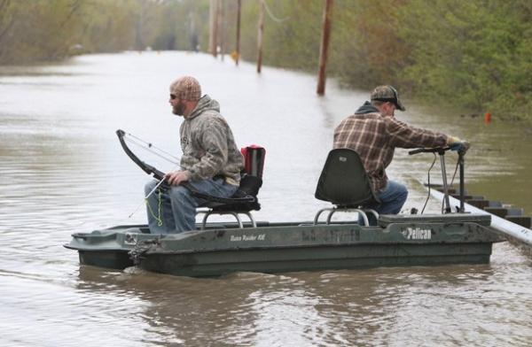 Homens são flagrados com arco e flecha pescando em rodovia alagada