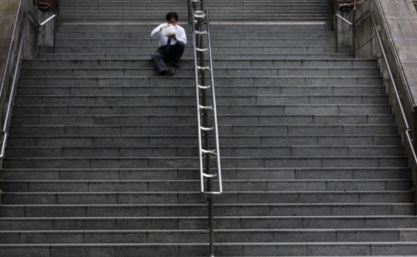 Solitário, homem almoça sozinho em escada de parque japonês