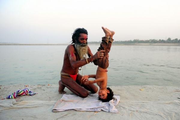 Indiano põe filho adotivo de cabeça para baixo para ensiná-lo ioga
