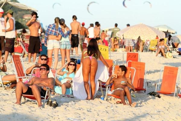 Nicole Bahls reforça o bronzeado em dia de praia e atraí olhares indiscretos
