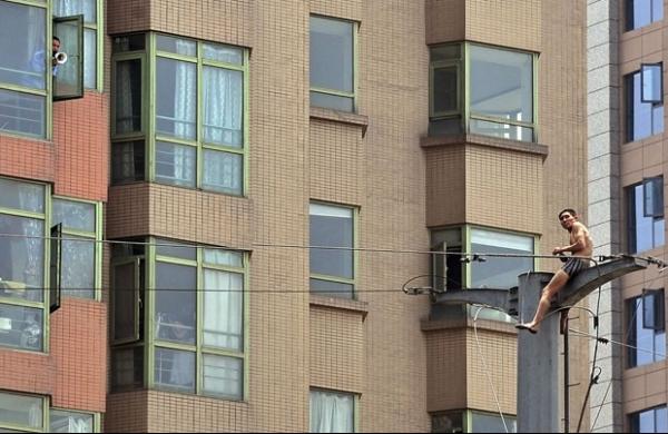 Homem escala poste, ameaça se jogar na China, mas depois desiste
