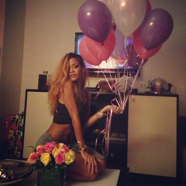 Com a barriga de fora, Rihanna beija bolo em  formato de batom