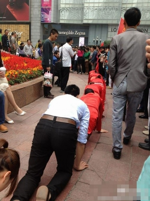 Empresa coloca funcionários para engatinhar em praça pública