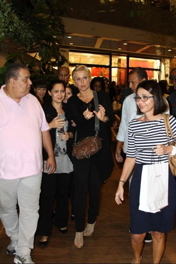 Xuxa faz sucesso com fãs no shopping e leva criança no colo