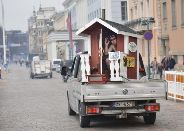 Homem acena de sauna móvel ao ser transportado em rua da Finlândia