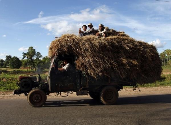 Trabalhadores viajam em cima de veículo supercarregado em Mianmar