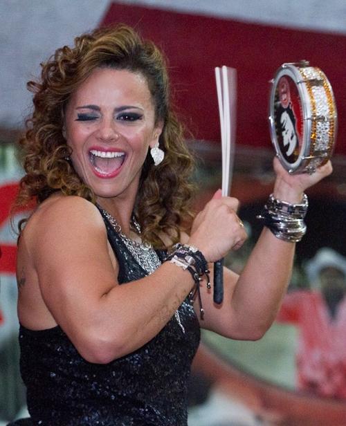 Viviane Araújo vai de shortinho a quadra de samba e toca tamborim
