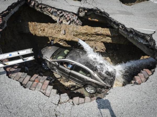 Buraco se abre no asfalto e