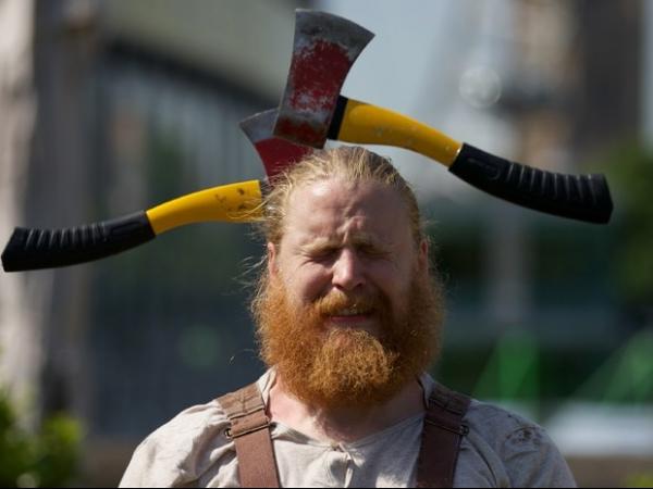 Artista circense faz caretas ao quase ser atingido por machados voadores