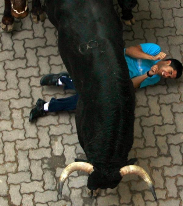 Touro passa por cima de corredor em ruas lotadas no 3º dia de festival em Pamplona, Espanha