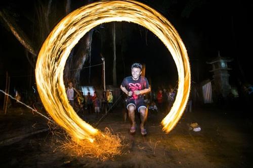 Indonésios se arriscam pulando uma corda em chamas durante uma festa