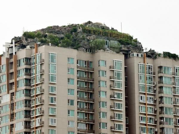 Chinês constrói mansão de pedra no topo de prédio e causa polêmica