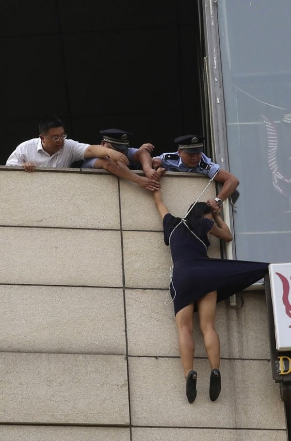 Policiais impedem que mulher se jogue de placa publicitária na China