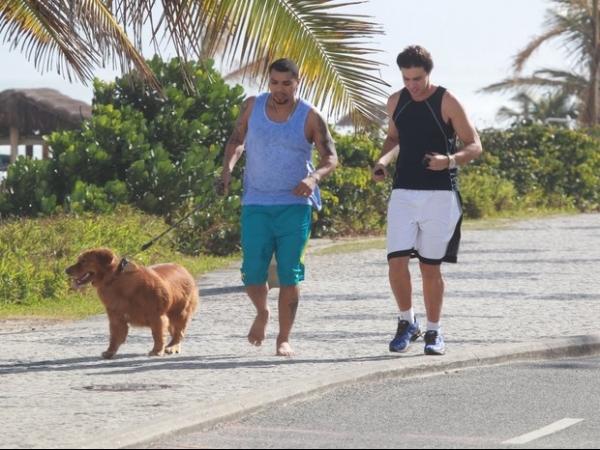 Naldo corre pela praia acompanhado de amigo e cachorro de estimação