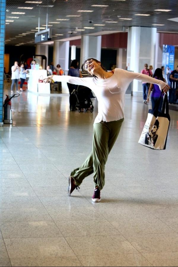Maria Casadevall brinca e faz careta para o fotógrafo em aeroporto
