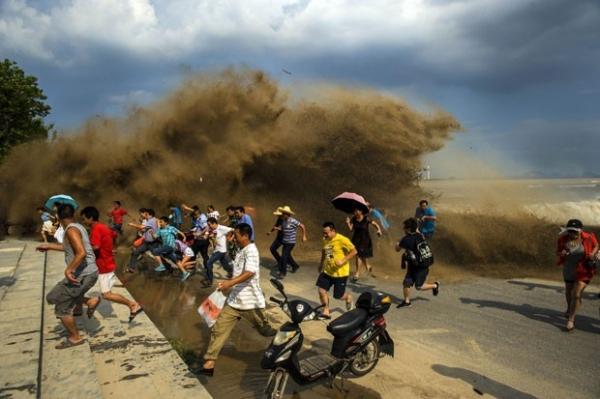 Chineses são surpreendidos por onda às margens do rio Qiantang
