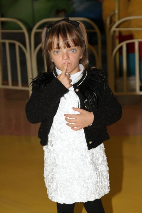Com blusa cheia de penas, Rafaella Justus se diverte em parque da Xuxa