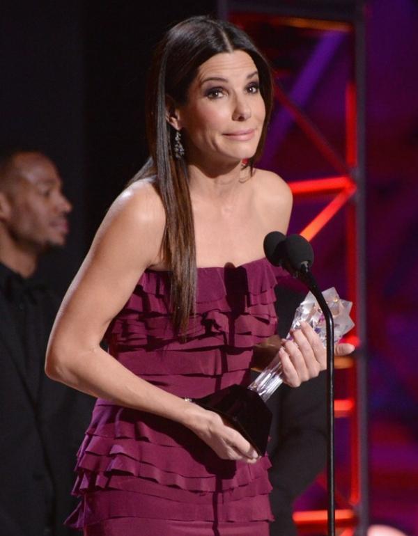 Interrompida em discurso de pr麥io, Sandra Bullock solta palavr縊 no palco