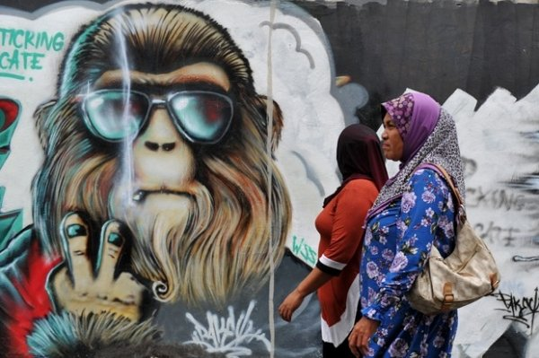 De óculos, grafite de macaco parece posar para foto na Malásia