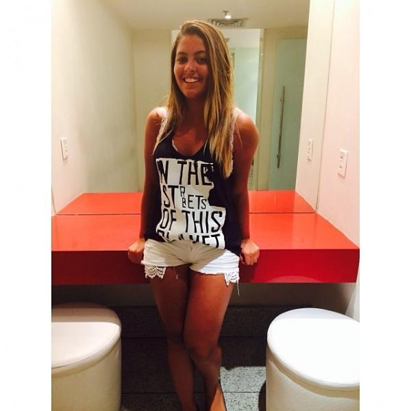 Danielle Favatto posa sorridente e de shortinho