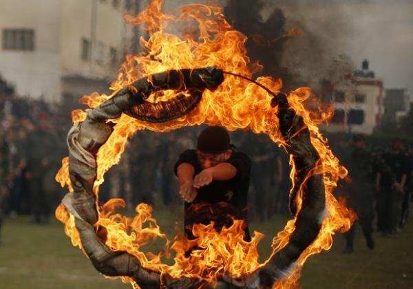Jovem palestino salta por círculo de fogo durante cerimônia militar