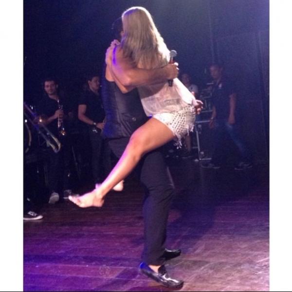 Carla Perez pula no colo de Xanddy durante show