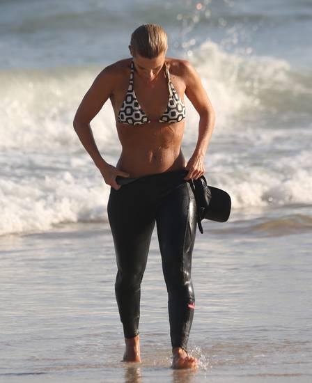 Carolina Dieckmann, de biquíni, se refresca com banho de mar após malhação na areia