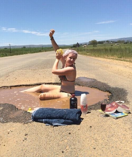 Professora faz protesto e toma banho em buraco de estrada