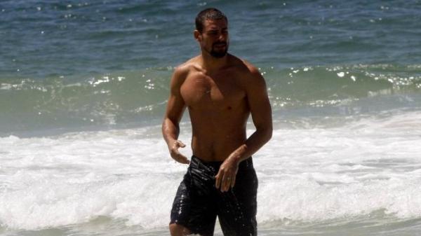 Cauã Reymond mima a filha, Sofia, na praia, e impressiona pela boa forma física