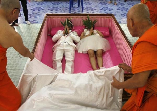 Rec駑-casados deitam em caix縊 rosa para atrair boa sorte na Tail穗dia