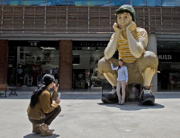 Mulher posa com escultura gigante do personagem
