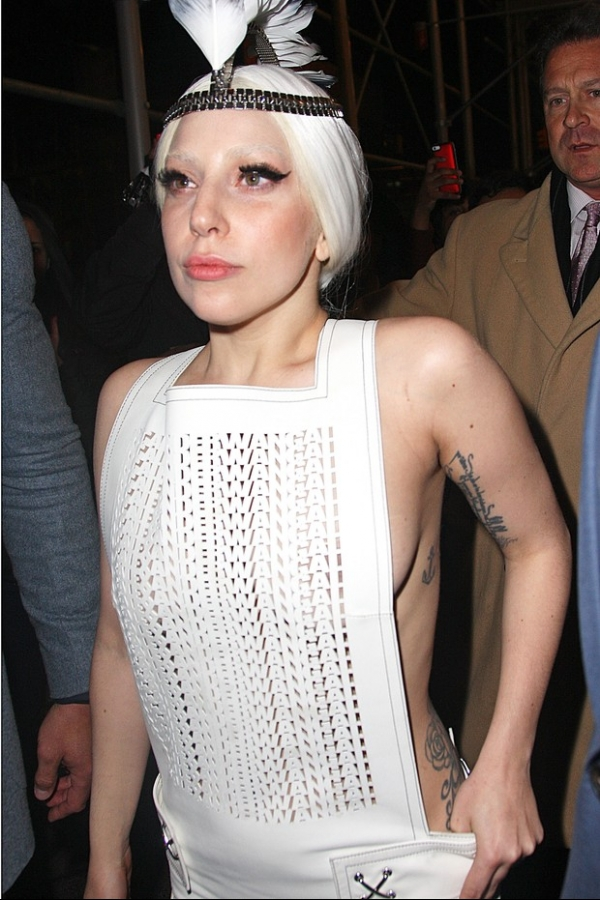 Sem suti, Lady Gaga usa look com penacho na cabe軋 e atende f縱
