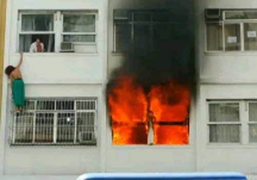 Mulher se arrisca para fugir de incêndio em prédio