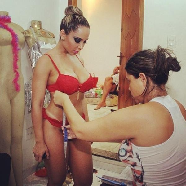 De lingerie, Mulher Melão posa fazendo últimos ajustes para desfile