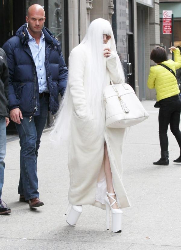 Lady Gaga se equilibra com salto imenso e esconde rosto com peruca