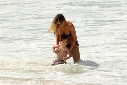 Letícia Birkheuer é traída por biquíni tomara que caia na praia com filho