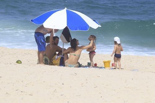 Com sutiã comportado, Priscila Fantin vai à praia com o filho Romeo e amigos