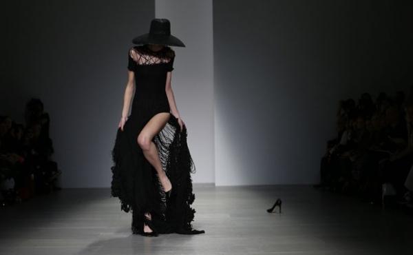 Modelo prende sapato de salto alto no vestido em desfile na Inglaterra
