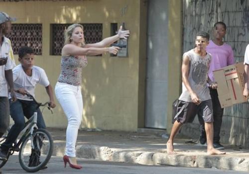 Mulher sai de carro e aponta arma para grupo