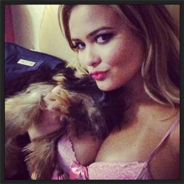De camisola decotada, Geisy Arruda tenta dar remédio para cãozinho