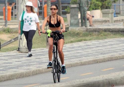 Com a barriga sarada, Anna Lima pedala pela orla do Leblon