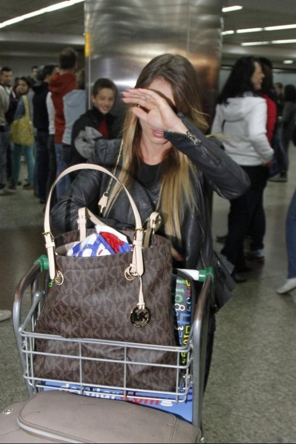 Miss Bumbum detida em Portugal chega ao Brasil e esconde o rosto