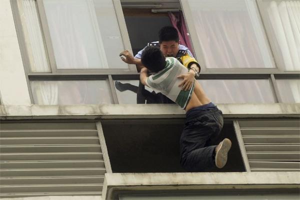 Policial segura homem que tenta se jogar de edifício na China; veja foto