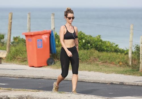 De top e barriga de fora, Juliana Didone caminha em orla carioca